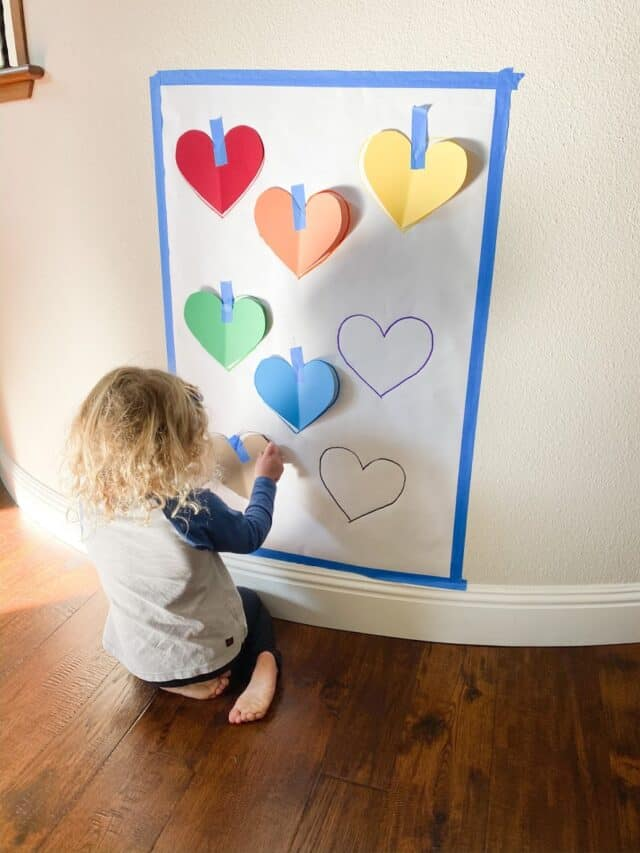 girl sticking hearts on the wall with tape