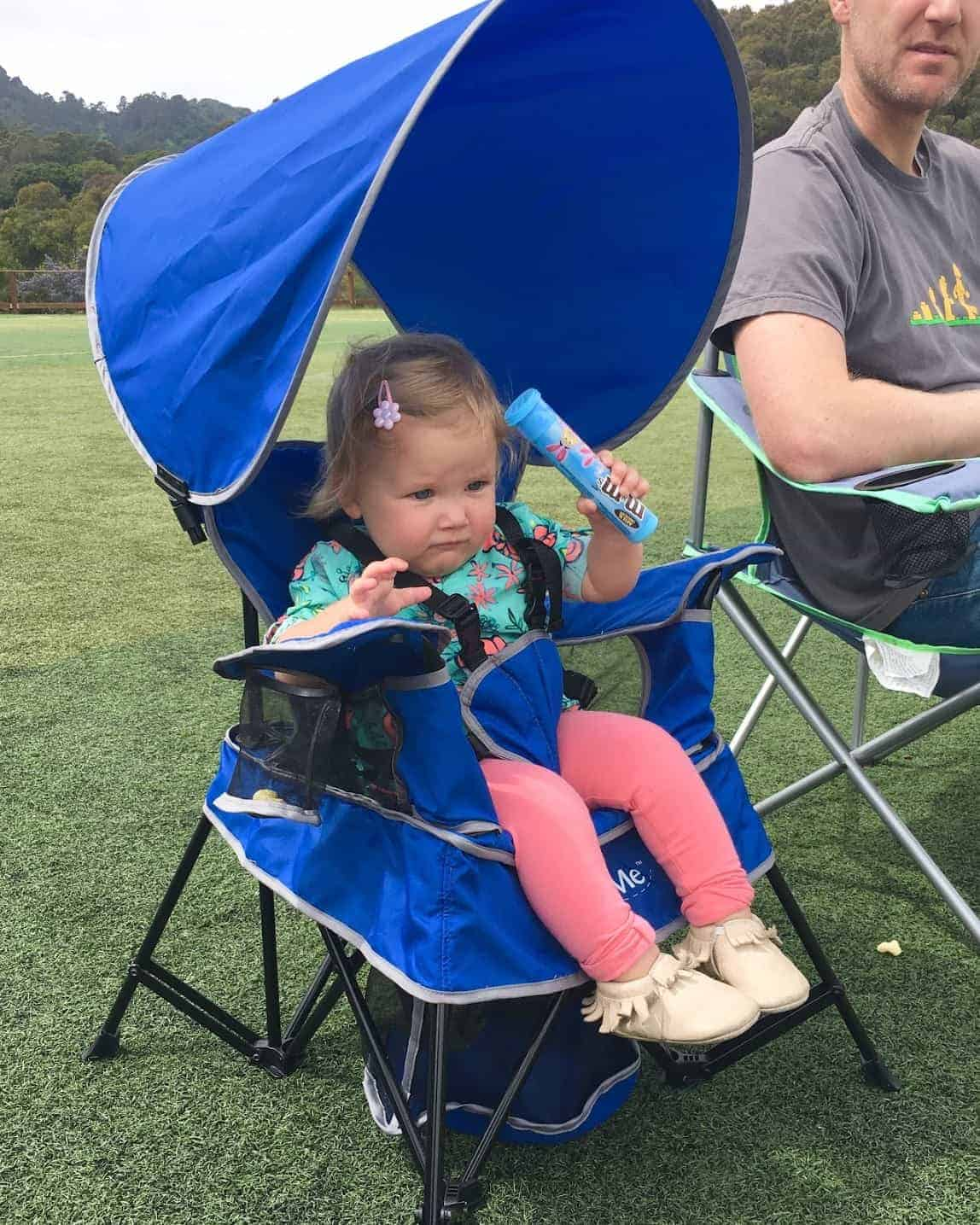 toddler girl sitting in a camping chair with 5 point harness, holding M&Ms