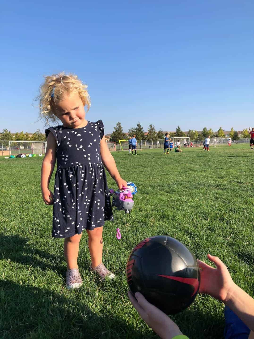 toddler girl holding a Paw Patrol toy watching soccer practice on a grass field