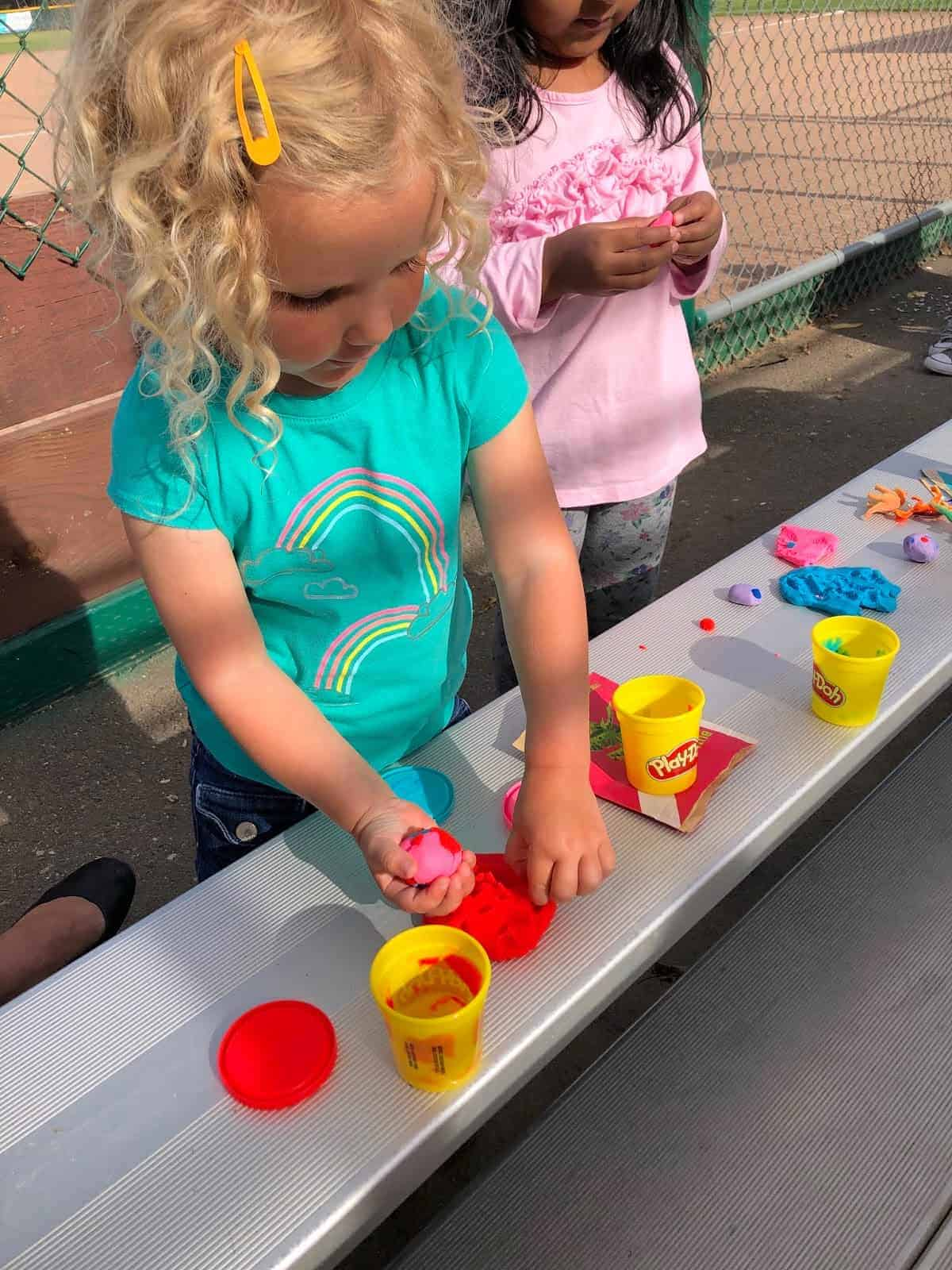 two girls playing with playdough on a baseball field bleacher