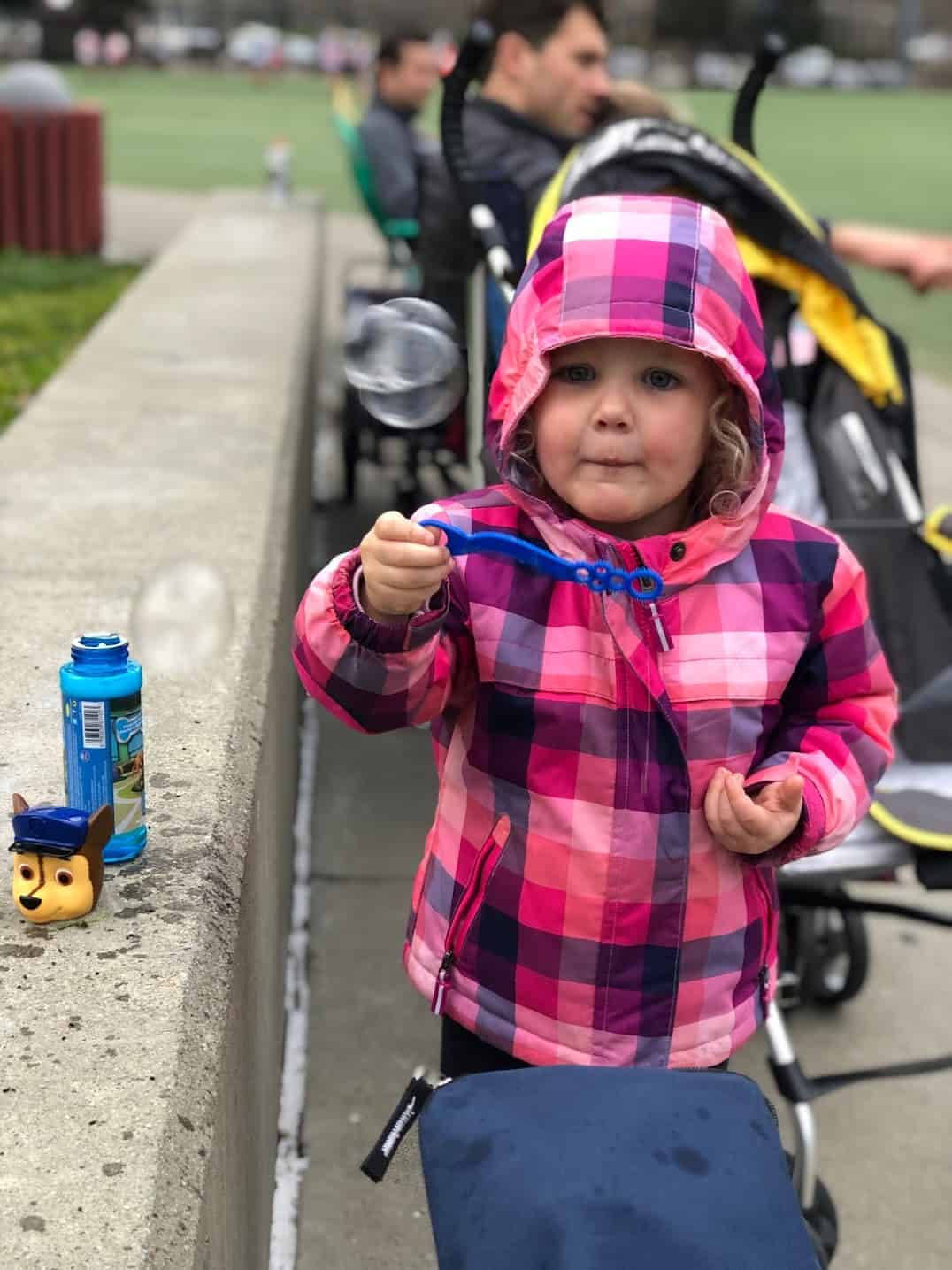 little girl wearing a winter coat blowing bubbles on the sidelines of a baseball game