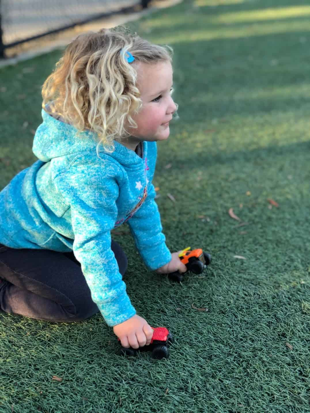 toddler girl holding two toy trucks watching her sibling's soccer game