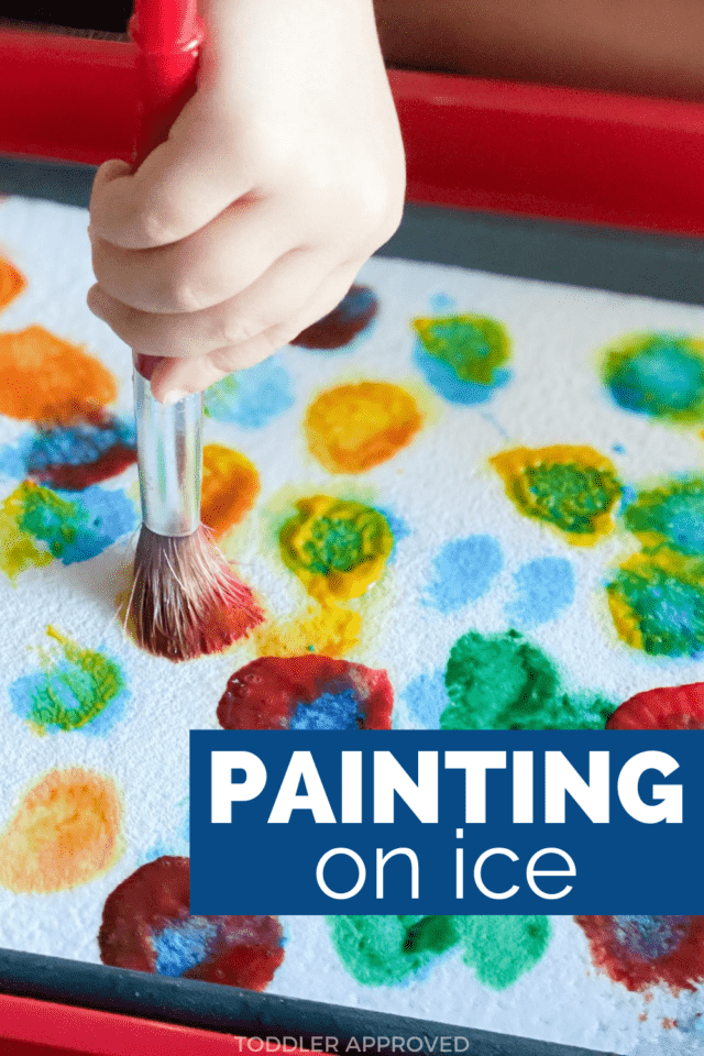 little girl's hand holding paintbrush and painting on ice with paint