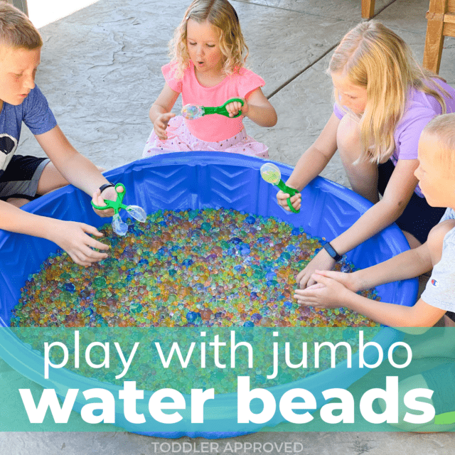 four kids playing with jumbo water beads in a blue baby pool