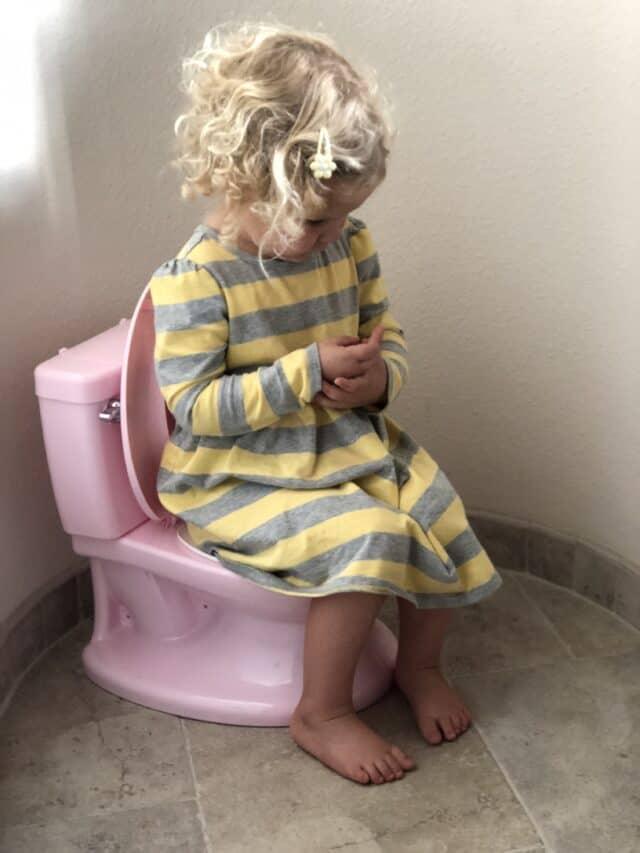 little girl sitting on a pretend potty