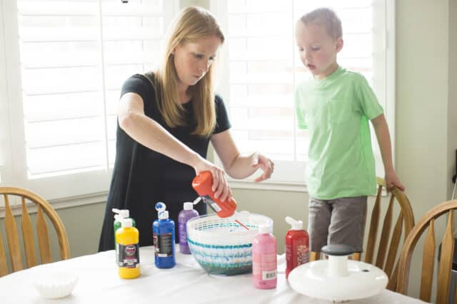 mom squirting washable tempera paint into a salad spinner