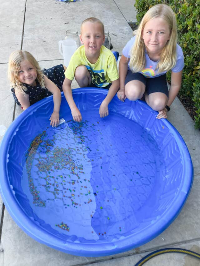 three kids sitting by a baby pool with water beads