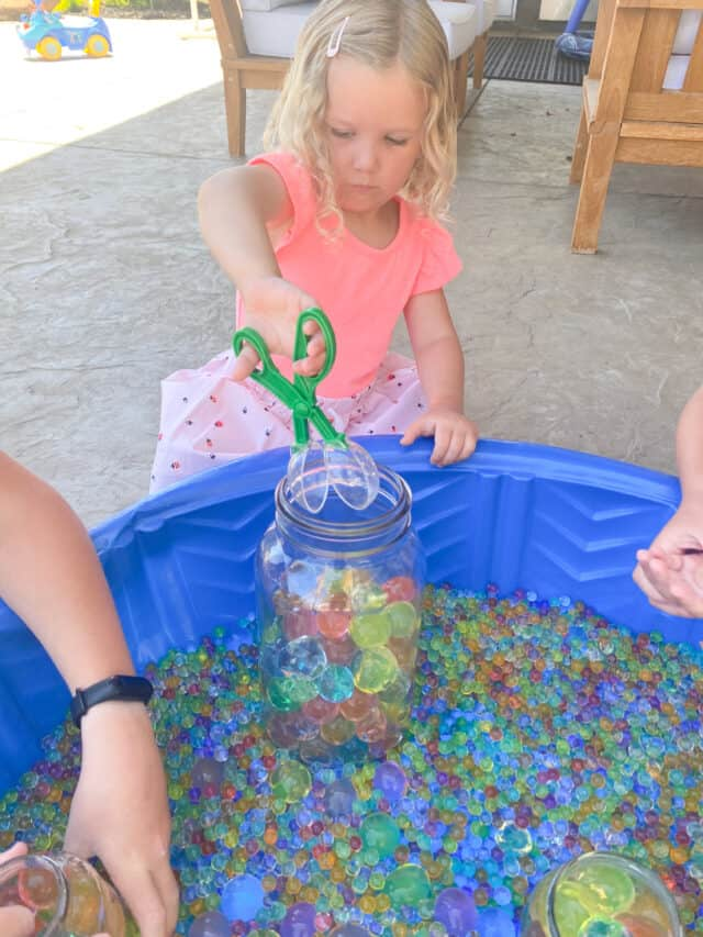 little girl using a scissor scoop with water beads