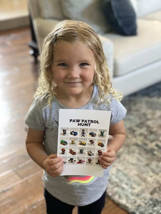 girl smiling holding a Paw Patrol scavenger hunt card