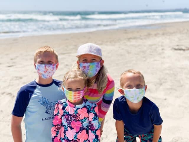 kids wearing tie dye masks at the beach
