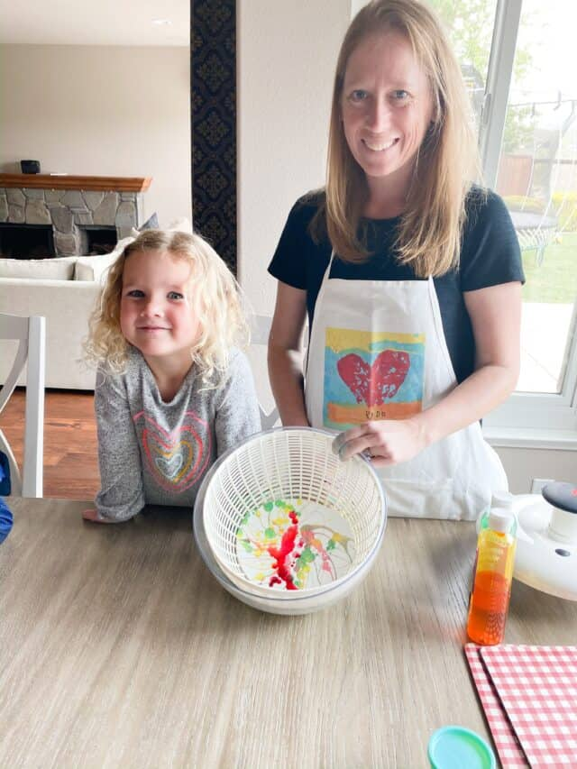 mom and daughter holiday up a salad spinner filled with a colorful painted coffee filter