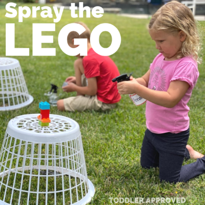 girl spraying the LEGO brick tower with a spray bottle