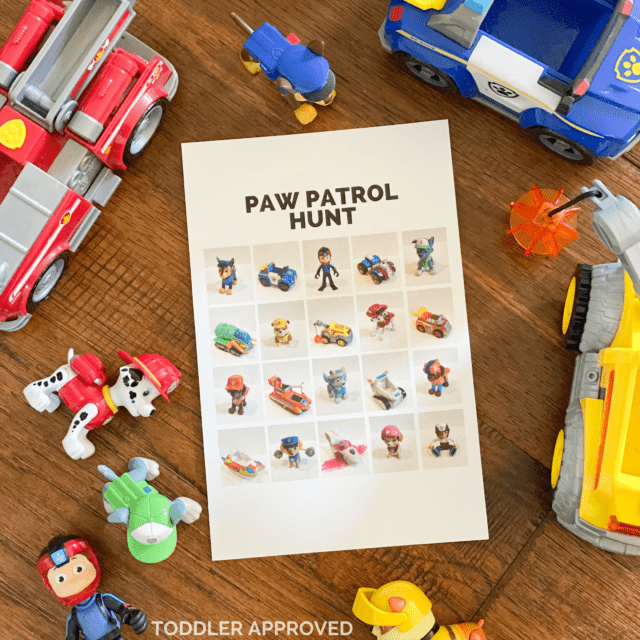 Paw Patrol toys on the floor along with a paper that has Paw Patrol photos on it.