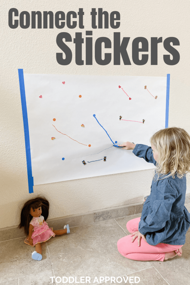 girl drawing a line on a large piece of paper from one sticker to another with a marker