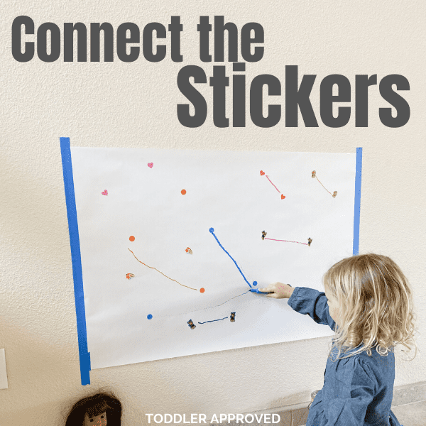girl drawing lines on a paper from one sticker to another