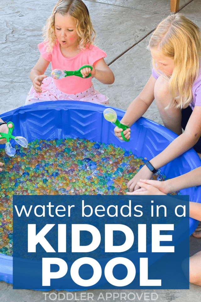 two kids playing with water beads in a kiddie pool