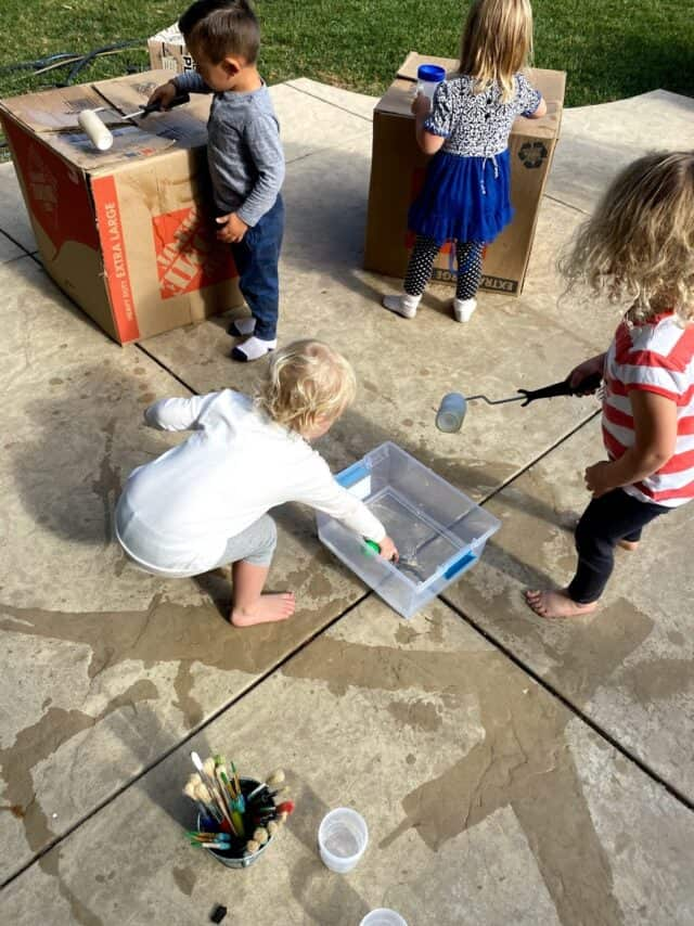 kids painting boxes with water