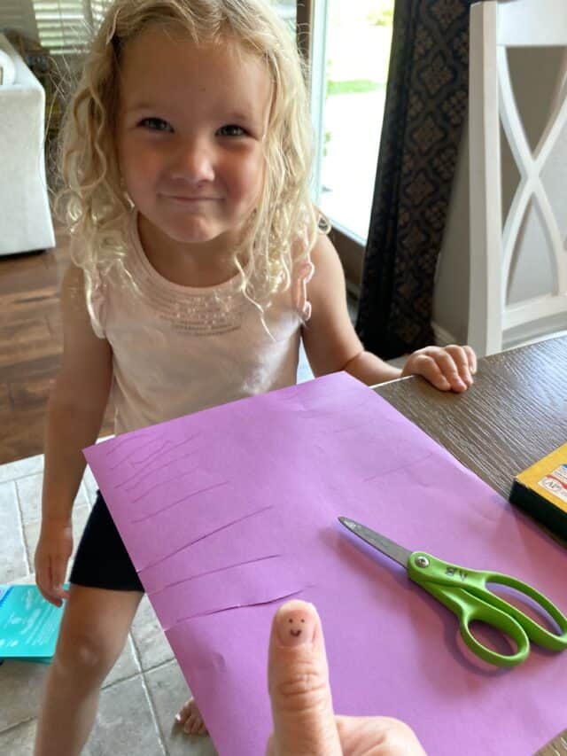 cutting activity made by a preschooler on purple paper
