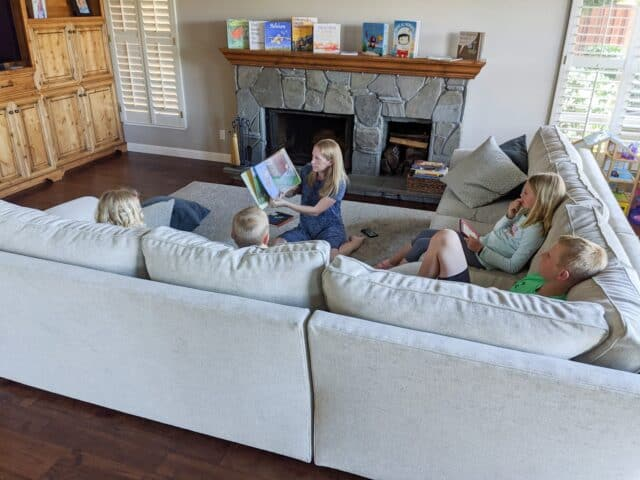 woman reading a book with four kids listening on the couch