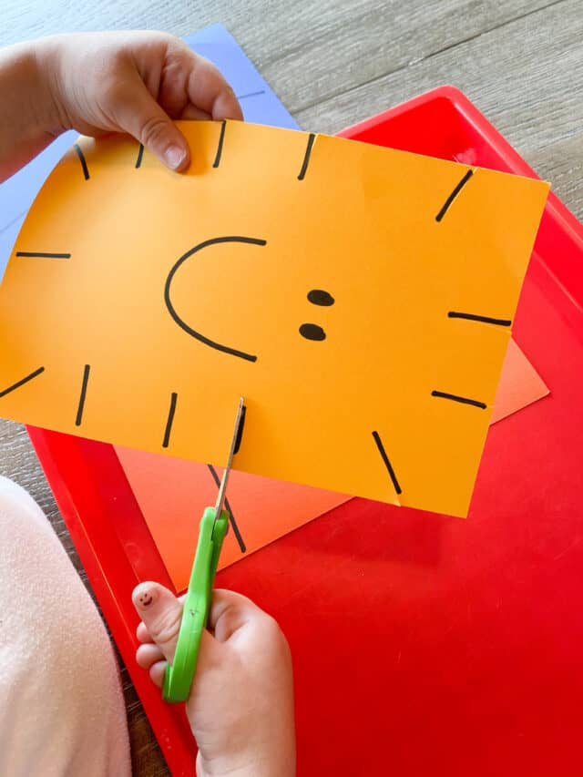 girl cutting a yellow paper with a smiley face on her thumb