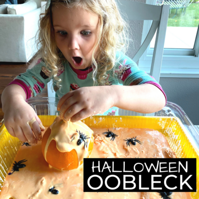 Girl playing with orange oobleck and plastic spiders