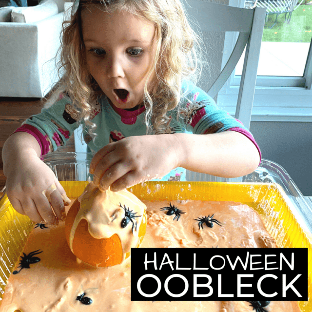 Girl playing with orange oobleck and pumpkins and plastic spiders