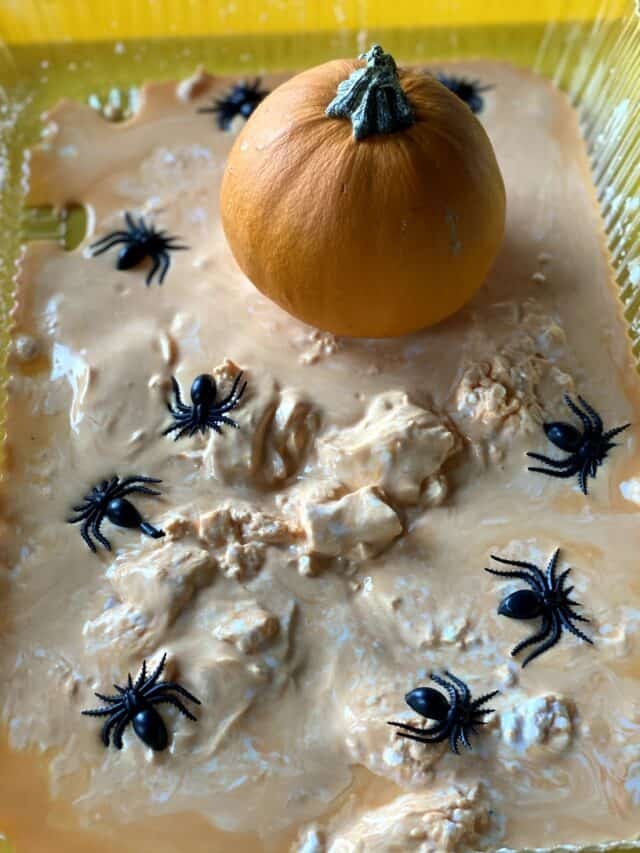 pumpkin and spiders sitting in orange oobleck