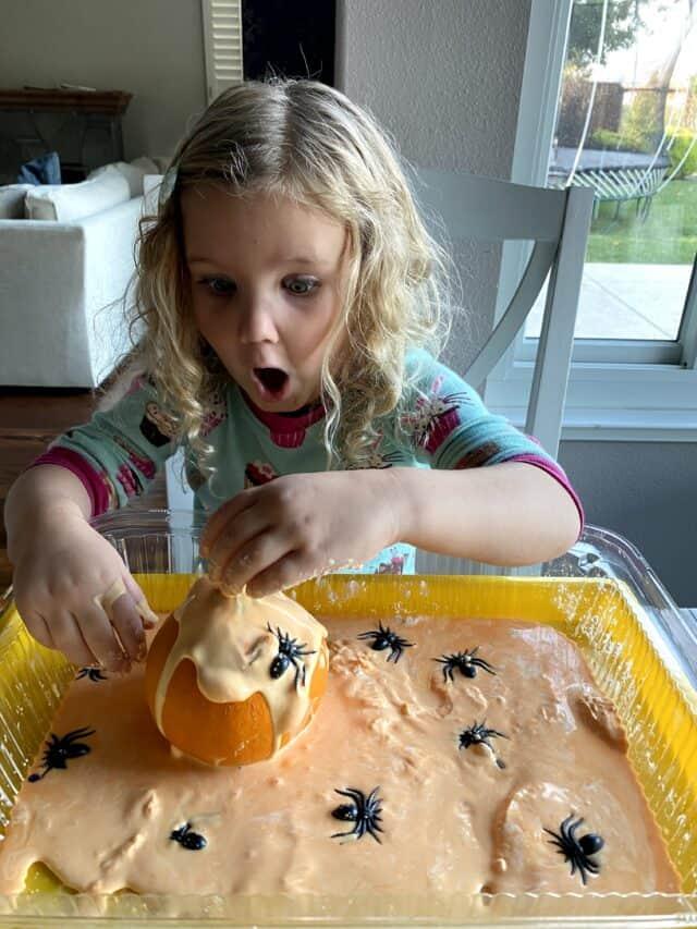 surprised girl looking at orange oobleck and pumpkin