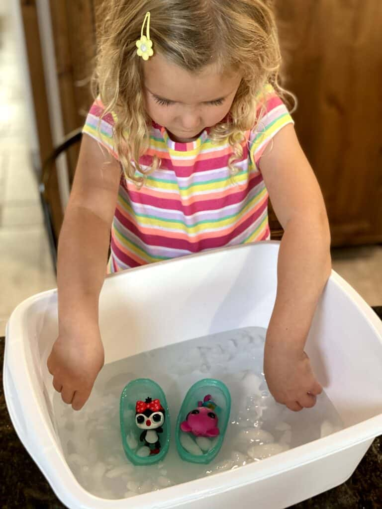 Girl playing with two Baby born pet toys in an ice bath
