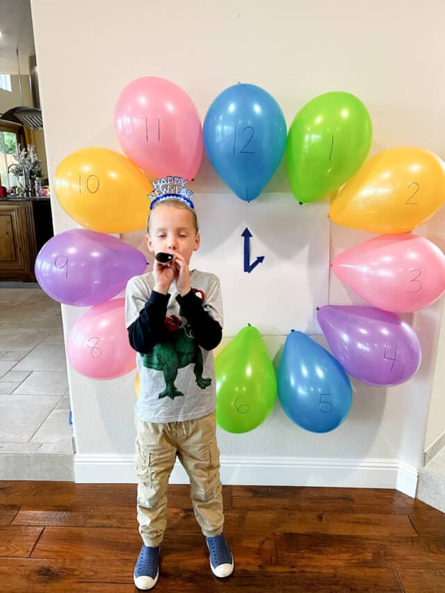 Boy blowing a New Years blower with a colorful balloon clock behind him.