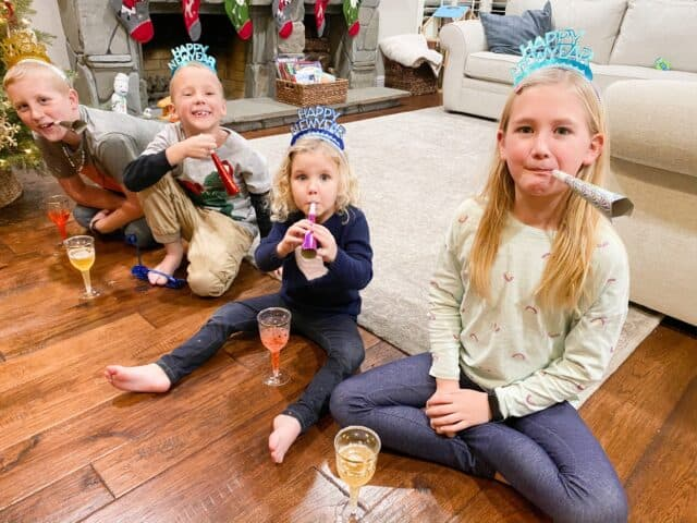 Kids celebrating New Years with a party blower, crowns, and sparkling cider.