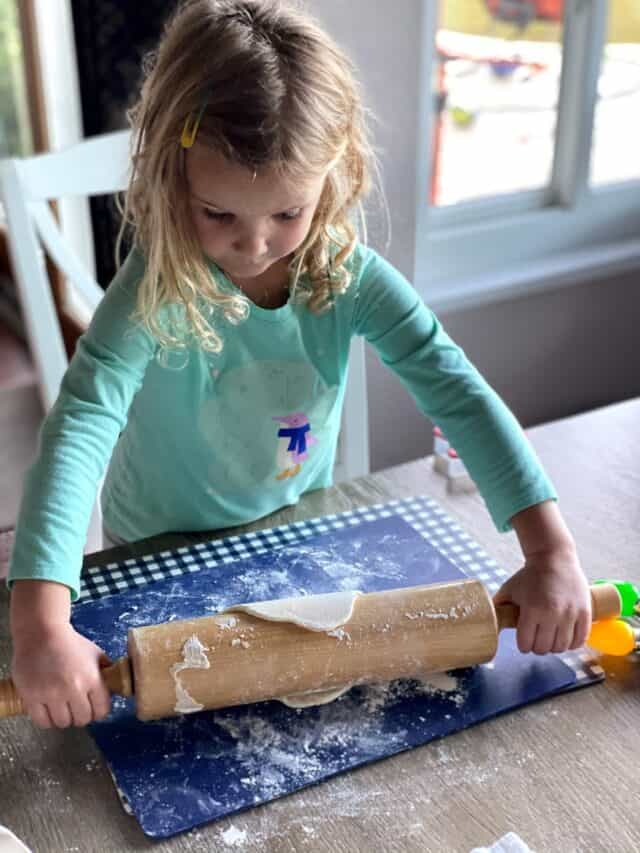 girl rolling out salt dough with a rolling pin