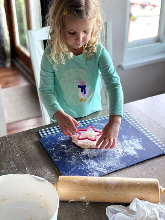 girl cutting dough with star cookie cutter