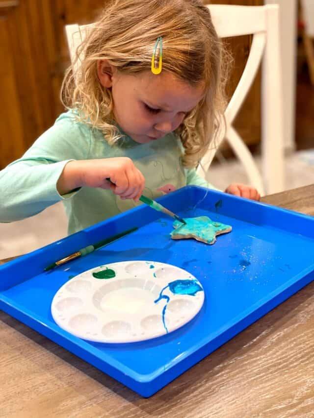 girl painting salt dough star ornaments