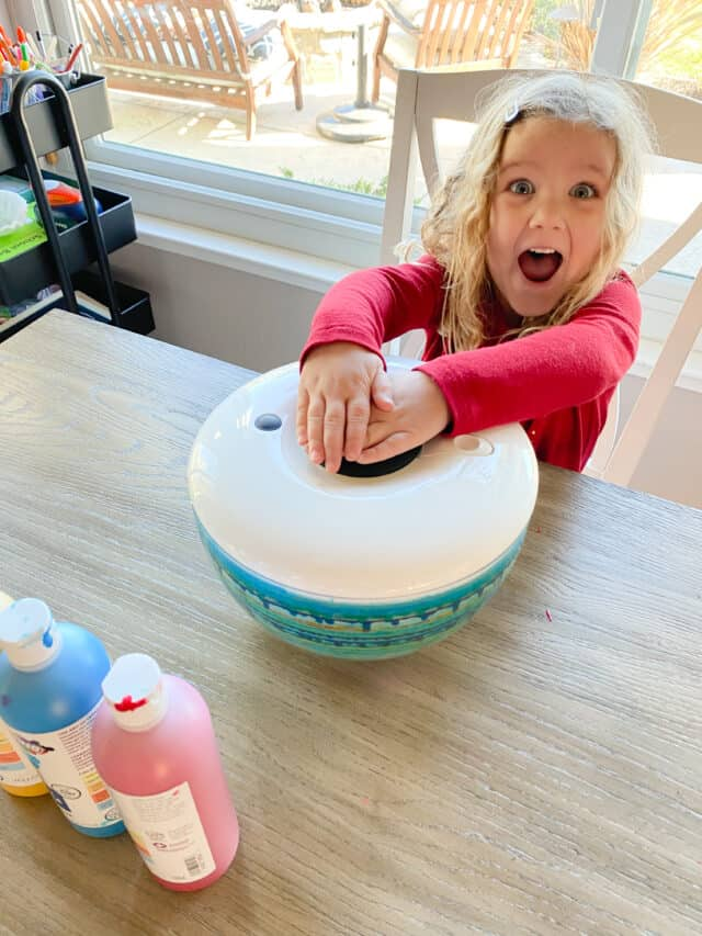 girl pushing down on the salad spinner