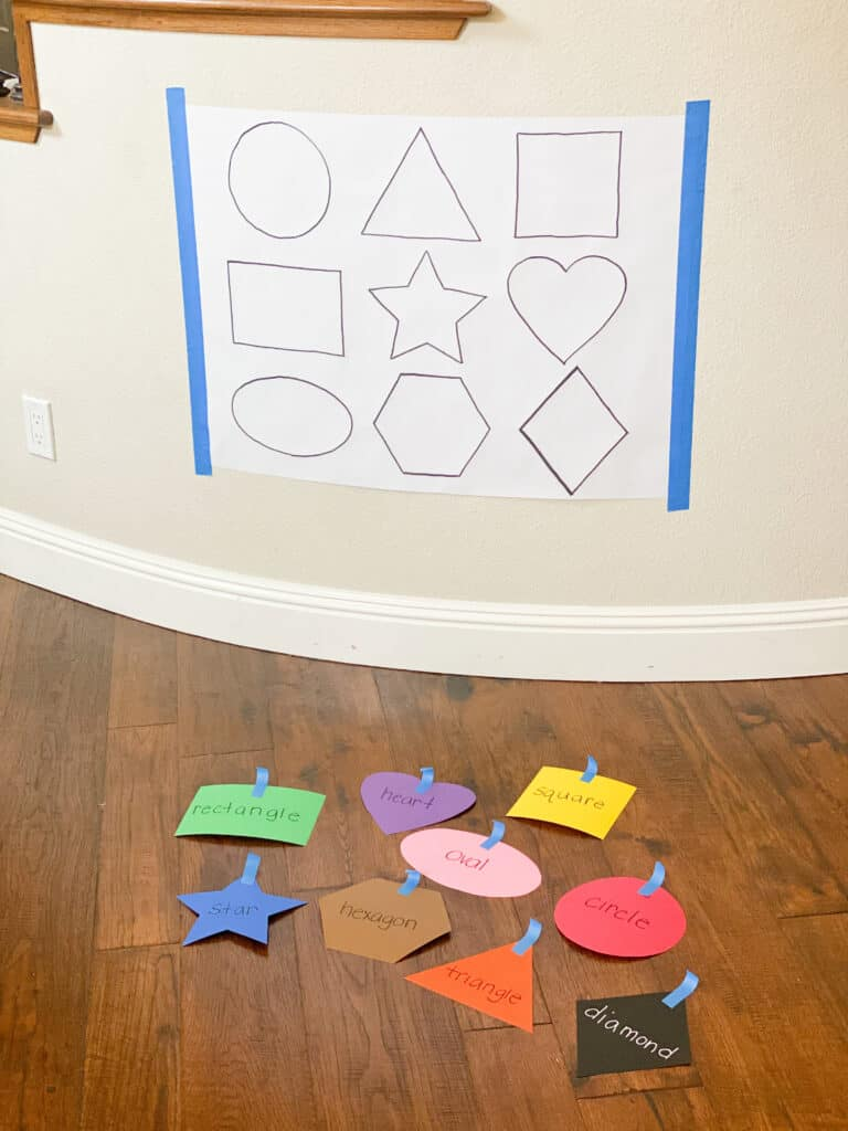 black and white paper with shapes on it and colored shape cut outs on the floor