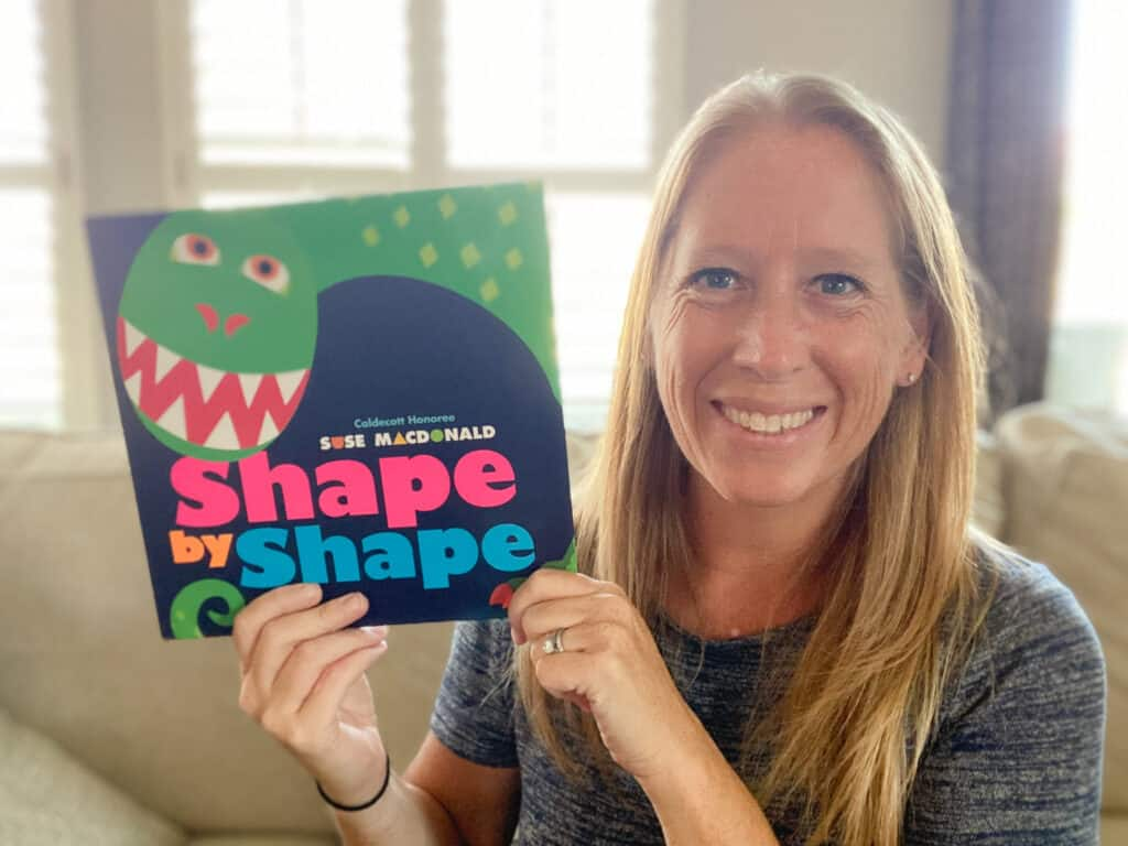white woman holding the book Shape by Shape by Suse Macdonald