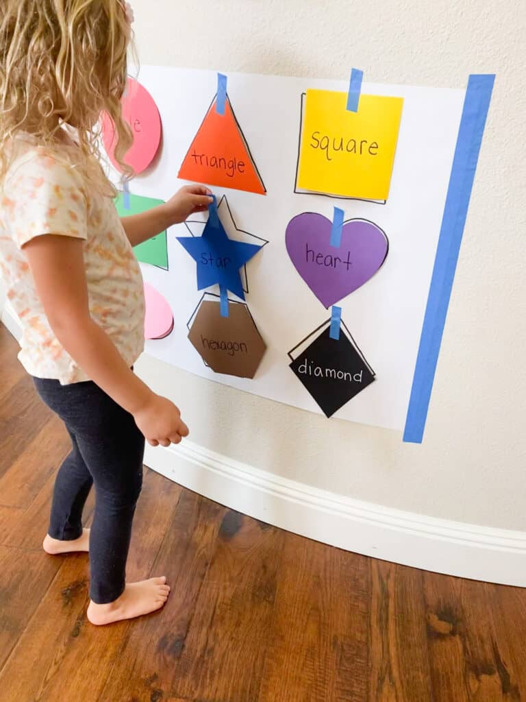 girl sticking a blue paper star onto the wall and matching it to a star shape