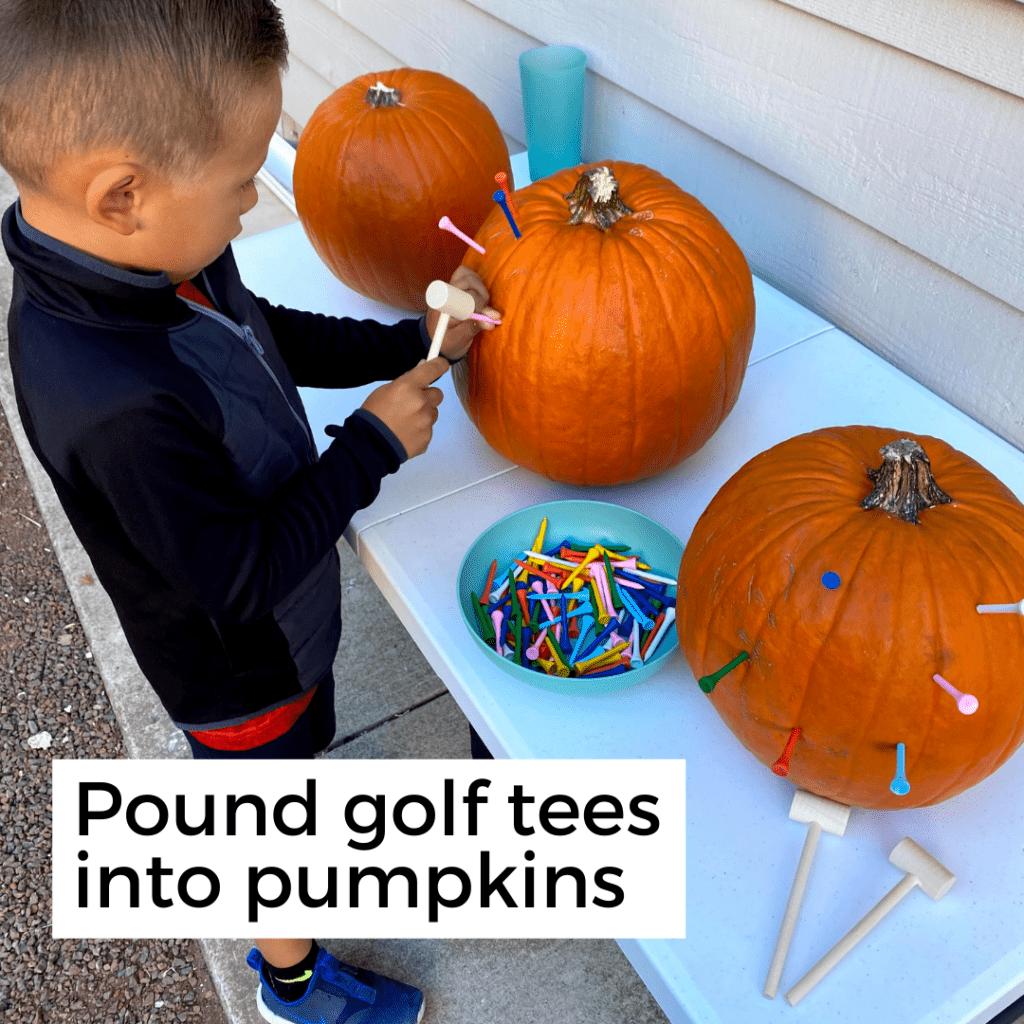 boy pounding colorful golf tees into a pumpkin